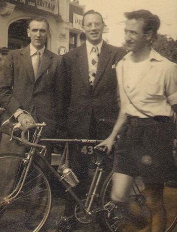 Tom and Monty with Stan Saunders Triumph bike at the start of the 1953 Tour of Britain ( a cyclist strays into shot) Brian Robinson was the only team member to complete the course.
