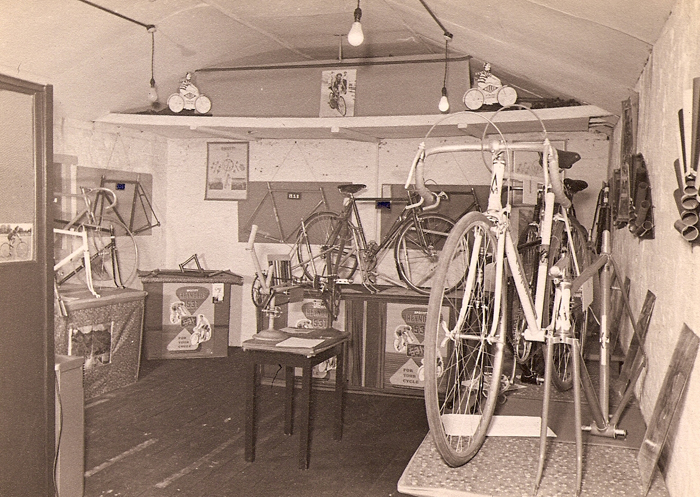 An image of Les Ephgrave's upstairs showroom decked out for an exhibition. The corner of an office partition can be seen on the left. The table in middle of showroom has two 'sub' frames to show gears, one an Osgear, the other a double-pulley gear - the cranks are fitted with pedals to enable the gears to be 'spun' by the prospective customer. On the table in the corner there is the mini main triangle of a frame, no doubt built to showcase the lugs, other builders did this but not on such a small scale, this looks as if it would fit into a briefcase but I don't think Les employed reps. On the right-hand wall are frame tubes sprayed to display colour options. There are plenty of Reynolds 531 posters on show, no doubt supplied by Reynolds for the event, and a selection of frames and built machines to whet the customers appetite. Against the rear wall is a display unit with a complete machine displayed on top (in front of two frames hanging on the wall), it is possible to make out a womens 'open' frame in front of the complete machine on this unit. The complete machine and (Italia?) frame to the right have the 'A' headbadge as used on early machines.