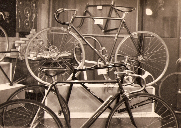 Another display with an Ephgrave in the foreground fitted with a trike conversion, with fixed wheel and one brake. Possibly the conversion was ordered by a customer unless Ephgrave acted as agents for the conversion. Behind there is a road frame set with BB, forks, headset and seat pin fitted as was the norm. Next on display is a complete track 'iron' set up in true 50's style with low stem and short seat pin showing. This machine has a large 5-pin inch-pitch chainset and drive. The wheels look like sprint rims on Airlites, Brooks saddle (possibly Sprinter) and a beautifully set up pair of bars on a long steel stem. It has close clearance as would be expected on a pure track machine. There are three other frames and, just showing, two more complete machines. On the display in the corner are various boxed components and several chainsets