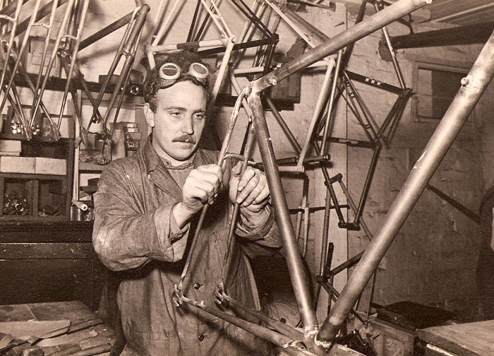 Fred Greaves (1949-55), one of Les's craftsmen at work in the workshop on a road frame with gear boss and cable eyes. Here he is sighting up the seatstay brake bridge before brazing commences. Strangely this bridge has no drilling for brake - see frames hanging on left in the background. Seeing a frame built like this shows how much cleaning-up has to be done before finishing and painting (see below). If you see a frame sand-blasted before a respray there is just a pencil-thin line of braze showing at the lug edges. In the background, a selection of track and road frames in various states of finish.