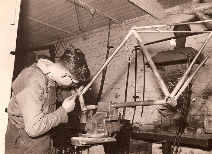 One of the 'filers' cleaning up a frame after brazing. After the frames were brazed the areas around the lugs were sandblasted to remove flux and residues from the brazing operation which can be seen clearly in the image above. This was done to make the filing down of the lugs easier, the filer is working on the headlugs, the seat cluster and bottom bracket are still to be tackled. (Roger Chamberlain) The frame is held in the vice using blocks of some soft material (lead?) shaped to hold the frame without damaging it. There is what looks like a waist-high small brazing hearth against the wall. Note the 'torch' aflame near the chimney cowl.