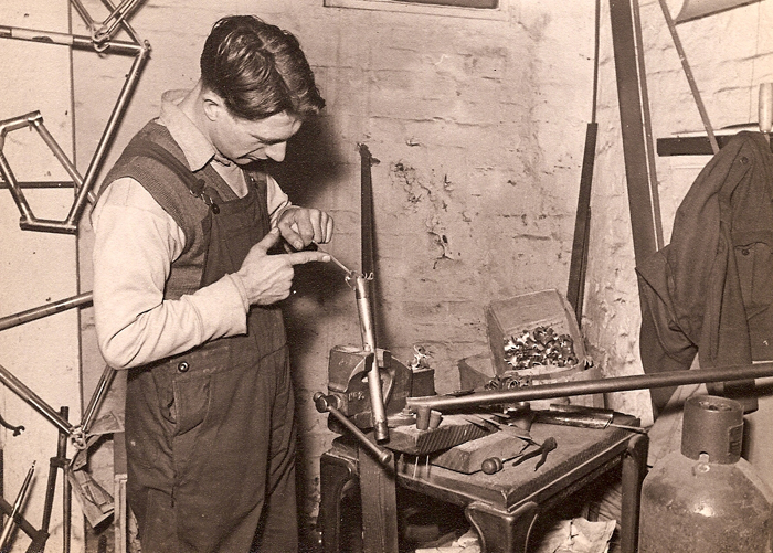 Here is another 'filer' trusted with the job of filing the lugs, for which Ephgraves are famous. This one held on a piece of tubing in the vice to give just the right height for working on. The operater is using a small round file with a wooden or cork handle for comfort. There are several of these files of different sizes on the table. Note the box of lugs waiting for a final finish as well as odd ones already filed on the vice and worktop. I wonder if this chap has returned from his national service as there is a battledress blouse hanging on the wall.