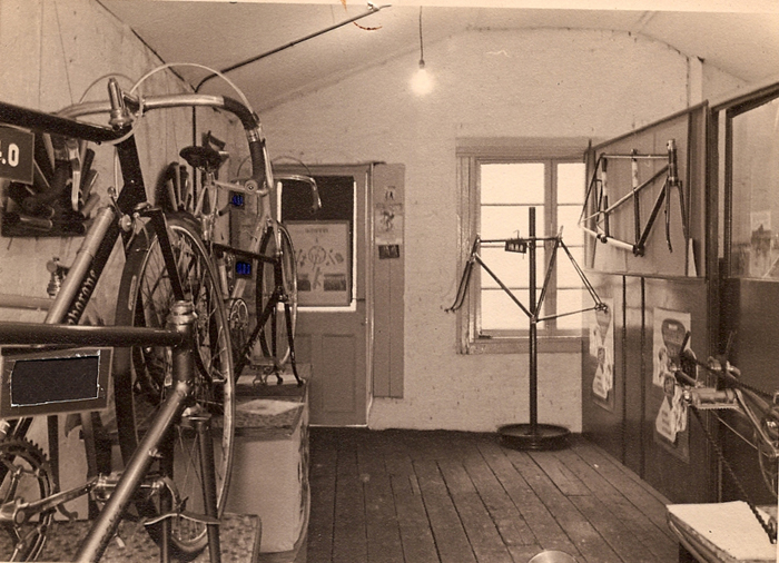 The other end of the showroom shown above with a selection of machines and frames on offer. There is a better view of the sub-frame built to display a working Osgear. On the right-hand office partition wall hangs an Ephgrave tandem with straight seat tubes. A road frame with gear hanger is on a display stand in front of the window. To the left, a road frame, with Simplex gear boss in foreground, behind this a built-up road machine with flint-catchers and gears including Simplex? double chainring and Simplex lever. Another frame and built-up machine behind that. The above two images show either end of one showroom, which begs the question as to whether Les had two showrooms in addition to the workshop. The two images below don't relate to the ones above although the roofline in the lower one is similar.