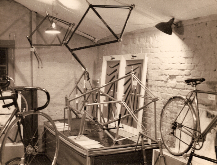 Two tandems in one picture of this showroom (in addition to the one in the second picture which has a long diagonal tube from head to rear seat tube where it splits into an extra set of stays). In this corner an USWB track frame with curved seat tube, the other with straight seat tube. Two road frames hang from the ceiling and two more are on the stand with the tandems. Other frames cannot be identified but the track iron is also in the above image. A display case on the right-hand wall shows forks of diffrent profile and rake alongside a display of chainstays.