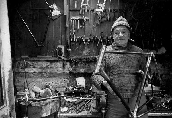 Dick Morris shown in his workshop with the brazing hearth to the left of the image with a pair of forks and a torch hanging on the edge