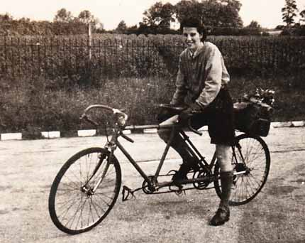 The Jack Holland built tandem during a tour with his wife Edith, shown here steadying the machine from the stoker's 'cockpit'