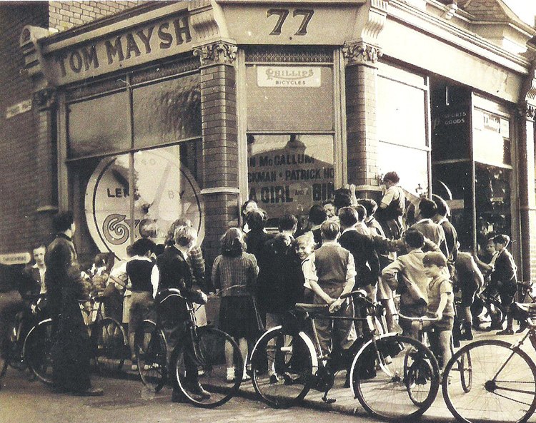 Here you can see a crowd of excited cyclists watching roller racing, which was a popular sport at this time, 1949 The dial connected to the rollers and showing the progress of the competitors can be seen on the left. If you look closely inside the shop, you will see an advertisement for the film, A Boy, a Girl and a Bike, which starred Honor Blackman and Diana Dors. When the film was shown at Palmers Green (I think the Gaumont) Diana Dors came to the cinema and Dad met her on the stage to promote the film. Diana was 18 at the time. I can remember the excitement although I was very young at the time.