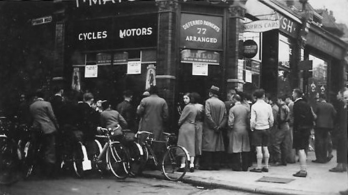 This is an image of the shop taken in 1938 and again a crowd watches roller racing in the window. Being pre-war Tom's father was advertising both cycles and motors with Morris cars sign. There was a large workshop to the rear of the premises allowing room for car repairs.