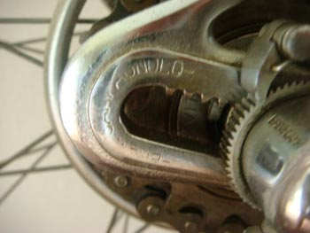 Close-up showing toothed ends to control wheel movement and ratchet to adjust chain tension