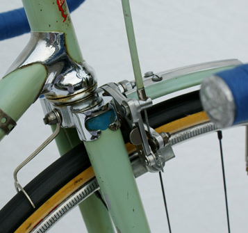 Two images of an unusual front mini-mudguard which pushes onto the brake bolt to secure as can be seen in left image.