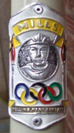 A F Mills head badge showing track credentials and Olympic rings