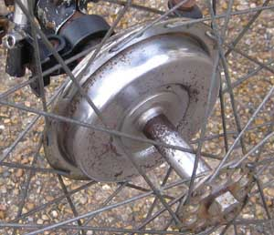 Two views of a hub brake on rear axle of trike showing anchor point on right image