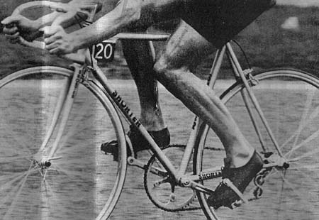 Alf Engers with his aerodynamic time-trial bike.  Brake levers mounted behind the tops of the bars. Front brake stirrup on rear of fork crown. 28 spoked wheels