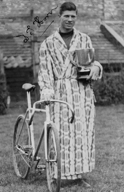 Dennis in his magnificent boldly-patterned dressing gown. Crossed over front with striped cord with tassels on end.