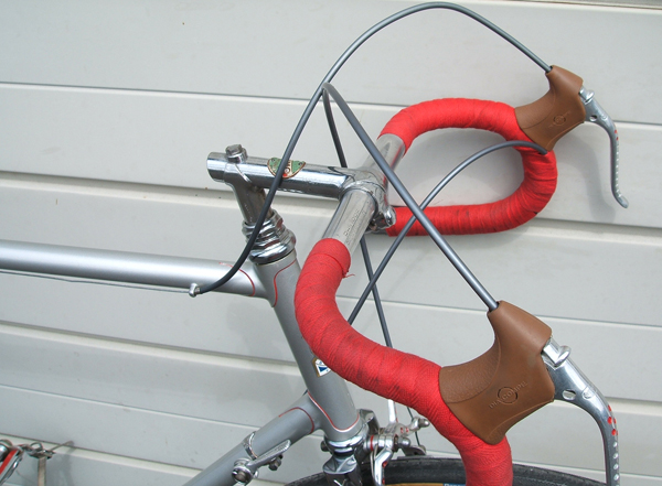 Front end showing Il Primo stem with Maes bars, drilled Weinmann levers Braze-on down tube changer for rear derailleur and bar-end for front Red lug lining on top edge of lugs