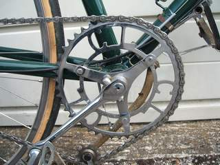 Two views of the Osgear tension arm with de-tensioner cable which runs through a short 'free-floating' silver outer cable. On this set-up the outer cable is held in a clip on the tension arm bracket. Riders of this era used to modify the jockey wheel on the tension arm by using the Cyclo version as here.