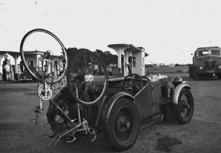 Ready to go racing, the bike has one bar-end gear lever plus one down-tube, both fitted on right-hand side. Early 1970s MG 'M' sports car.