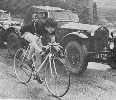 Ruth Smith (North Lancs CC) passing a Lancia Lambda in the 1955 25-mile Womens' Championship in an era when women were still not allowed to enter men's events. She is riding fixed with one brake to the front wheel and the obligatory bell mounted on the stem. (See note from Laurie Weeks about the Lancia at bottom of this page)